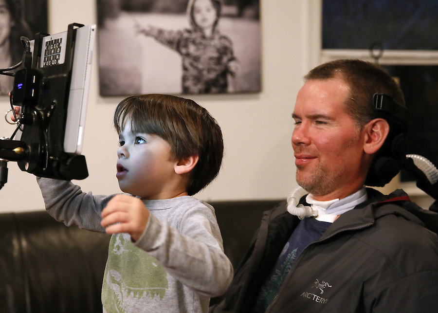 In this Monday, Jan. 18, 2016 photo, former New Orleans Saints NFL football player Steve Gleason watches as his four-year-old son, Rivers, plays on his father's tablet during an interview in New Orleans. (AP Photo/Jonathan Bachman)
