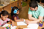 Education Preschool Headstart 3-4 year olds young male teacher working with girl art activity drawing