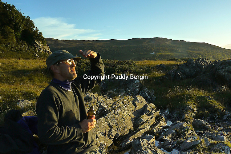 Nearing the end of the coastal walk on Arran which finishes at Lochranza. Having a well deserved beer while watching the sunset.<br /> <br /> Stock Photo by Paddy Bergin