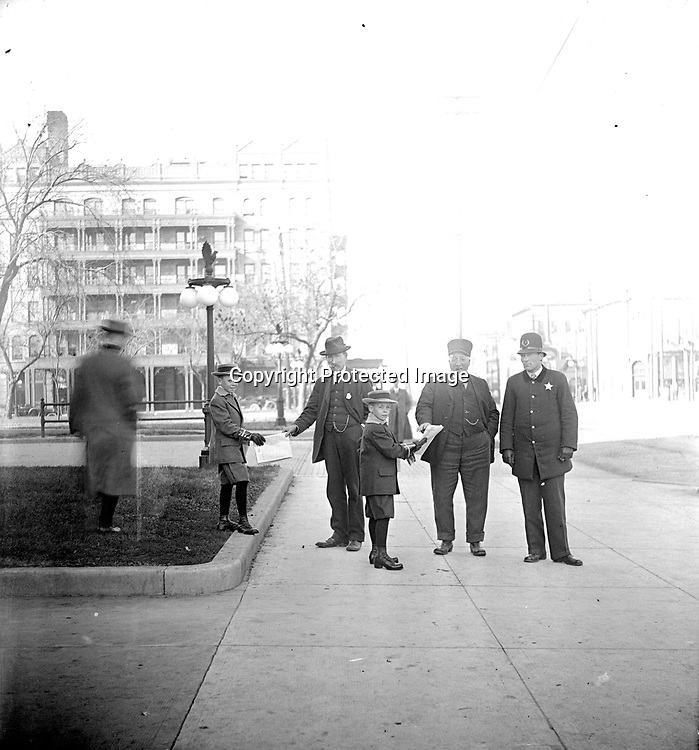 NEWSBOYS AND PATRONS. The men and newsboys of the lower image on page 17 have stepped down from the courthouse entrance to pose in the act of selling their papers on the sidewalk north of the courthouse and post office. The office of the Lincoln Journal newspaper (Nebraska State Journal in the 1860s, Lincoln Journal Star in 2008) was located across P Street to the north of the courthouse and post office since the 1880s and remains there today. Lincoln Hotel is in the left background, west across Ninth Street from Government Square. The light pole with four globes has a bronze eagle finial with raised wings. Those lights were installed around Government Square in 1907.<br /> <br /> Photographs taken on black and white glass negatives by African American photographer(s) John Johnson and Earl McWilliams from 1910 to 1925 in Lincoln, Nebraska. Douglas Keister has 280 5x7 glass negatives taken by these photographers. Larger scans available on request.
