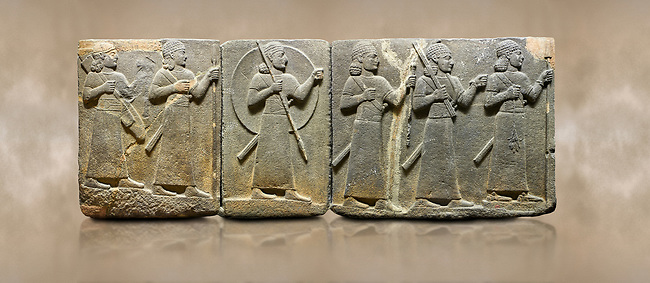 Photo of Hittite relief sculpted orthostat stone panel of Royal Buttress Basalt, Karkamıs, (Kargamıs), Carchemish (Karkemish), 900-700 B.C. Warriors. Anatolian Civilisations Museum, Ankara, Turkey.<br /> <br /> Right panel - Three figures each with a long dress, a thick belt and curly hair. The figure in front holds a spear with a broken tip in his left hand and a leafy branch in his right hand. The figure in the middle made his left hand a fist, and he carries a tool with his right hand at the level of his head. They are followed with a figure holding a sceptre in his left hand. All three have each a long sword at their waist. <br /> <br /> Against a brown art background.