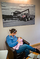 """A mother breastfeeding her baby of eight months in a cafe at a visitor farm park .<br /> <br /> Image from the breastfeeding collection of the """"We Do It In Public"""" documentary photography picture library project: <br />  www.breastfeedinginpublic.co.uk<br /> <br /> <br /> Gloucestershire, England, UK<br /> 30/09/2013<br /> <br /> © Paul Carter / wdiip.co.uk"""