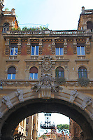 Rome, piazza Buenos Aires: The typical building made in the form of an arc, with its windows, which delimitates the characteristic quarter designed by Gino Coppedé. There is an old chandelier at the center of the arc and other typical buildings of the quarter are visible on the background.