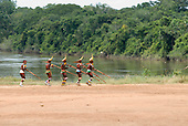 Xingu Indigenous Park, Mato Grosso State, Brazil. Aldeia Afukuri (Kuikuro). Festival of Taquara, warriors playing Taquara bamboo flutes at the river bank.