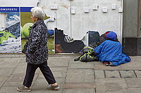 Pictured: A woman walks past a homeless man in Newport, Wales, UK. Thursday 14 February 209<br /> Re: The city of Newport is preparing to host the FA Cup match between Newport County and Manchester City at Rodney Parade, Newport, Wales, UK.