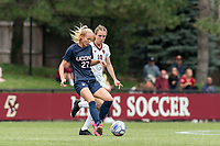 NEWTON, MA - AUGUST 29: Abbey Jones #27 of University of Connecticut passes the ball as Emily Knous #10 of Boston College defends during a game between University of Connecticut and Boston College at Newton Campus Soccer Field on August 29, 2021 in Newton, Massachusetts.