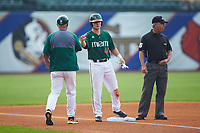 Michael Burns (44) of the Miami Hurricanes bumps fists with third base coach Gino DiMare (6) during the game against the North Carolina Tar Heels in the second semifinal of the 2017 ACC Baseball Championship at Louisville Slugger Field on May 27, 2017 in Louisville, Kentucky. The Tar Heels defeated the Hurricanes 12-4. (Brian Westerholt/Four Seam Images)