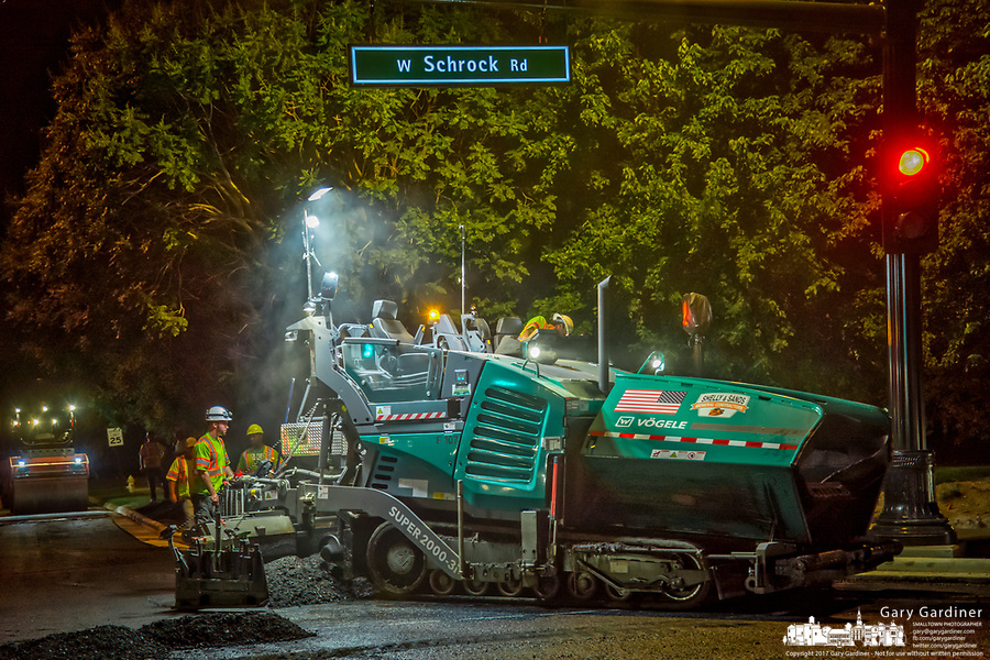 Worker laying asphalt on last section of the State and Schrock Road intersection upgrades.