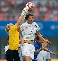 New Zealand goalkeeper Jenny Bindon clears the ball  away from her defender (5) Abby Erceg during first round play in the 2008 Beijing Olympics at Qinhuangdao, China. .  Japan tied New Zealand, 2-2, at Qinhuangdao Stadium.