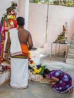 Hindu Priest and Young Worshiper at Hindu Sri Maha Muneswarar Temple, Kuala Lumpur, Malaysia.