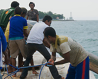 Timorese crew raises anchor by hand on a boat in Dili harbor, Timor-Leste (East Timor)