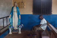 Nigeria. Enugu State. Awhun. Saint Luke's Catholic Parish. An Igbo man is seated on a wooden bench during a religious wedding ceremony. A plaster statue of the Virgin Mary stands up close to the wall. Two vases with plastic flowers are on the ground. Mary was a first-century BC Galilean Jewish woman and the mother of Jesus, according to the New Testament. The gospels of Matthew and Luke in the New Testament describe Mary as a virgin; according to Christian theology she conceived Jesus through the Holy Spirit while still a virgin. Mary has been venerated since early Christianity and is considered by millions to be the most meritorious saint of the religion. She is said to have miraculously appeared to believers many times over the centuries. 29.06.19 © 2019 Didier Ruef