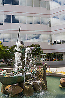 An office building's water fountain features a sculpture - an Australian Aborigine standing in a dugout canoe, a spear in one hand, a boomerang in the other.  In this image, a koala is perched on a rock to the right, and a frog sits on the boat's edge to the left.