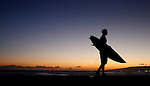 A surfer is silhouette in the evening twilight at Magic Island, Honolulu, Hawaii.