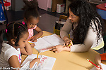 Education Preschool 4-5 year olds female teacher working with girl at sign-in period at start of day