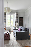 An African carved panel adds an interesting feature to one wall of this pale grey sitting room