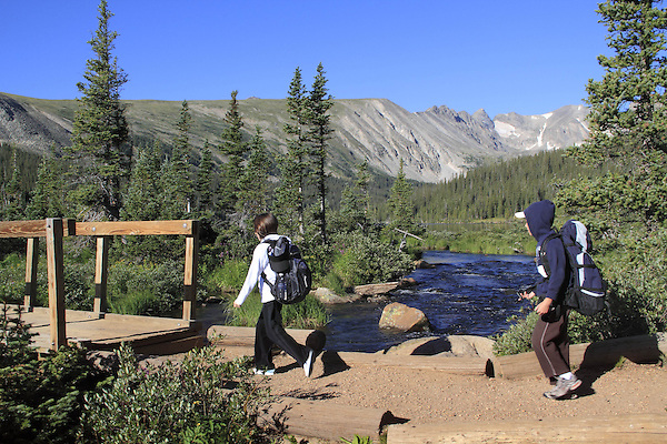 Girl and boy hiking in Indian Peaks Wilderness Area, west of Boulder, Colorado, USA. Guided photo tours to Indian Peaks.
