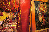 "India. Uttar Pradesh state. Allahabad. Maha Kumbh Mela. A Naga (naked) Sadhu sits on a carpet inside his tent in Sangam. Naga sadhdus were once warriors, that's why they still carry weapons, such as Trishula. A trishula is a type of Indian trident, commonly used as a Hindu religious symbol. The word means ""three spear"" in Sanskrit. In India, the term often refers to a short-handled weapon which may be mounted on a danda or staff. The trishula is wielded by the Hindu God Shiva. A drawing on the right with indian deities: Ram, Vishnu, Shiva and the cow. The Kumbh Mela, believed to be the largest religious gathering is held every 12 years on the banks of the 'Sangam'- the confluence of the holy rivers Ganga, Yamuna and the mythical Saraswati. In Hinduism, Sadhu (good; good man, holy man) denotes an ascetic, wandering monk. Sadhus are sanyasi, or renunciates, who have left behind all material attachments. They are renouncers who have chosen to live a life apart from or on the edges of society in order to focus on their own spiritual practice. The significance of nakedness is that they will not have any worldly ties to material belongings, even something as simple as clothes. A Sadhu is usually referred to as Baba by common people. The Maha (great) Kumbh Mela, which comes after 12 Purna Kumbh Mela, or 144 years, is always held at Allahabad. Uttar Pradesh (abbreviated U.P.) is a state located in northern India. 7.02.13 © 2013 Didier Ruef"