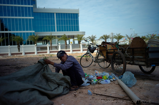A man sorts scavenged bottles for recycling in front of the building of the Laos Securities Exchange in Vientiane, Laos on March 25, 2011.
