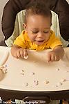 10 month old baby boy sitting in high chair pincer grasp