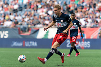 FOXBOROUGH, MA - AUGUST 8: Adam Buksa #9 of New England Revolution passes the ball during a game between Philadelphia Union and New England Revolution at Gillette Stadium on August 8, 2021 in Foxborough, Massachusetts.