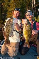 Men hoisting smallmouth bass