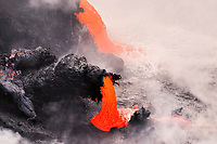 Lava pours into the sea out of a small lava hose, Waikupanaha ocean entry, Kilauea volcano, East of Hawaii, USA Volcanoes National Park, The Big Island of Hawaii, USA