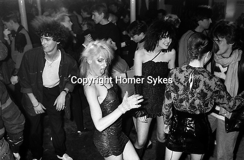 Blitz Kids New Romantics at The Blitz Club Covent Garden, London, England 1980.<br /> <br /> Girl in that dress is Wendy TigerPearson<br /> (Wendy Tiger Pearson) fashion student from Bournmouth and Poole College of Art. Later worked at Granny Takes a Trip in the Kings Road. She was a dancer at the Embassy nightclub in Bond Street, seen here strutting her stuff at the Blitz. Many years later can be found at a  London university working in administration. <br /> <br /> Girl with black bob hairstyle is Wendy May who was Billy Idol's girlfriend in the band Chelsea. Girl back view with black leather plastic skirt is Lorraine from the dance troupe Spoonoch. <br /> <br /> My ref 10a/4004/1980