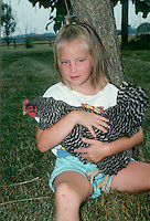Young girl holds her favorite chicken, a Silver Laced Wynadotte, while sitting in orchard, midwest USA
