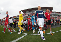 14 April 2012: Chivas USA forward Alejandro Moreno #15 and Toronto FC defender Richard Eckersley #27 lead their teams out during the opening ceremonies in a game between Chivas USA and Toronto FC at BMO Field in Toronto..Chivas USA won 1-0..