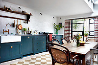 A Shaker-style kitchen by DeVol, with cabinets and larder painted in 'Studio Green' by Farrow & Ball, is furnished with a country refectory table and rattan-backed bentwood chairs