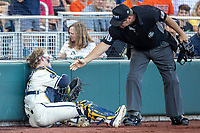 Michigan Wolverines catcher Joe Donovan (0) is helped up from the ground from home plate umpire Jeff Henrichs against the Vanderbilt Commodores during Game 1 of the NCAA College World Series Finals on June 24, 2019 at TD Ameritrade Park in Omaha, Nebraska. Michigan defeated Vanderbilt 7-4. (Andrew Woolley/Four Seam Images)