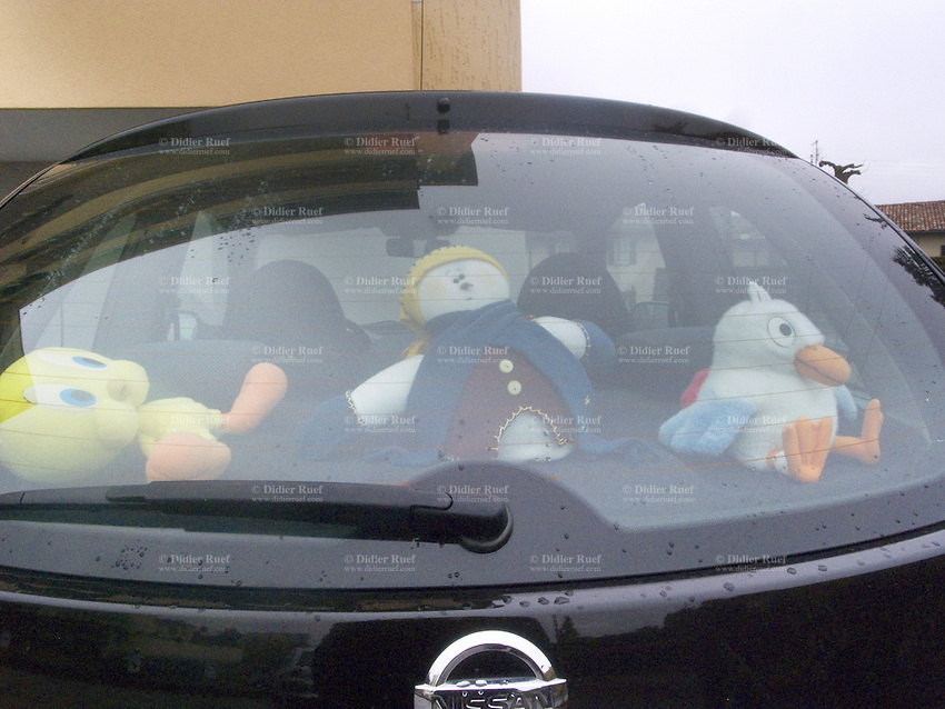 Switzerland. Canton Ticino. Vacallo. On the back window of a Nissan car, plush toys like Tweety, a doll and a stuffed animal. 21.03.10 © 2010 Didier Ruef