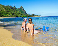 Honeymooners wearing snorkeling gear smile at each other in the shallow surf at Tunnels Beach on Kaua'i.