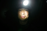 A coal miner is lit by a headlamp at one of the state-owned mines near Luoyang, Henan Province, China..