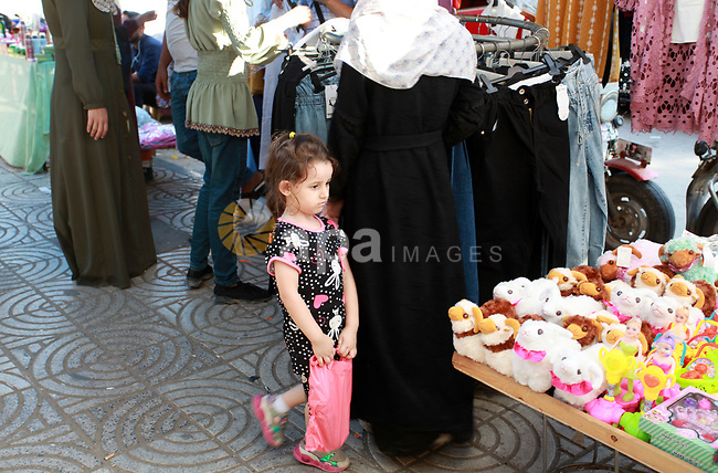 Palestinians shop ahead of Eid al-Adha festival, in Gaza city, on July 17, 2021. Israel allowed raw materials for critical industries into the Gaza Strip through Kerem Shalom. Until now, Israel has significantly limited the entrance of goods into the enclave following last month's 11-day conflict, saying it would only expand the type of products allowed into Gaza if the Hamas terror group, which rules the Strip, releases two Israeli civilians held in captivity, along with the remains of two soldiers. Photo by Omar Ashtawy