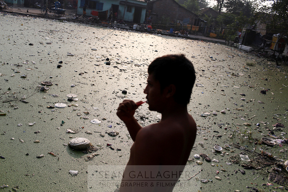 A man brushes his teeth in the Captain Bherry community in Kolkata. In the background a heavily polluted small pond in the centre of the resident's homes. November, 2013