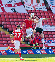 24th April 2021, Oakwell Stadium, Barnsley, Yorkshire, England; English Football League Championship Football, Barnsley FC versus Rotherham United; Mads Juel Andersen of Barnsley and Michael Smith of Rotherham challenge for a header whilst Alex Mowatt of Barnsley waits for the second ball