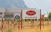 Sign saying Hercegovina Vino Plantaze along a tall barbed wire fence protecting the vineyard. Hercegovina Vino, Mostar. Federation Bosne i Hercegovine. Bosnia Herzegovina, Europe.