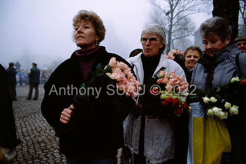 Lichterfelde, Berlin (West) and Teltow, Potsdam (East) crossing post, West Germany<br /> November 14, 1989 <br />  <br /> A West German women hold flowers to greet East Germans at the opening of the Berlin Wall. Germans gathered as the wall is dismantled and the East German government lifts travel and emigration restrictions to the West on November 9, 1989.