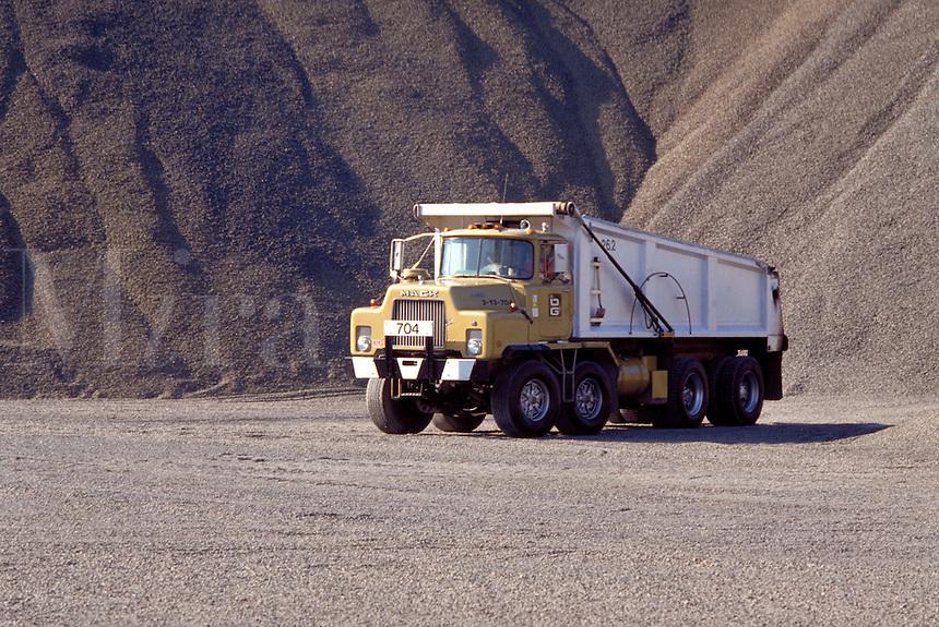 Mack 5 axle dumptruck close-up on gravel road, gravel mound background, horz. Southbury CT USA.