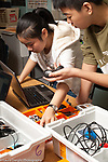 Education High School robotics elective male and female students checking parts against inventory