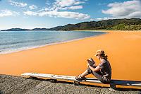 Young woman reading book on empty beach in Totaranui after sunrise on Abel Tasman Coast Track, Abel Tasman National Park, Nelson Region, South Island, New Zealand