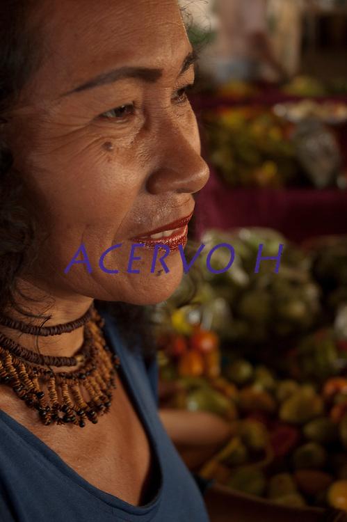 Carmézia, índia Macuxi, prepara a damorida, comida indígena a base de peixes ou caça temperada com forte molho apimentado.<br /> Comunidade indígena  Macuxí, Raposa Serra do Sol.<br /> Normandia, Roraima, Brasil.<br /> Foto Paulo Santos<br /> <br /> 2004 Carmézia Emiliano é indígena Macuxi e nasceu em 20 de abril na Guyana. Sua família imigrou para a aldeia Japó, no município de Normandia, estado de Roraima, Brasil, na década de 70 e desde 1988, ela reside em Boa Vista.<br /> <br /> A artista conquistou por quatro vezes o prêmio na Bienal de Arte Naif do Salão SESC de Piracicaba-SP e foi agraciada com o Prêmio Buriti da Amazônia de Preservação do Meio Ambiente, em 1996, na categoria revelação.<br /> <br /> Ela figura no topo da lista dos maiores artistas Naifs brasileiros. O estilo é conhecido por lançar obras com aquele aspecto inacabado, primitivo, até mesmo singelo e descompromissado.  A relação de Carmézia com a arte está intimamente relacionada com a sua trajetória. Ao conhecer as obras de arte e a vida da artista, têm-se a boa impressão de que Carmézia pinta a si própria, em vida e em memória.<br /> <br /> A mulher que nasceu e se criou na comunidade indígena, constituiu família com um pernambucano - Léo Malabarista - entrou com ele no mundo do circo e se integrou na cena urbana sem jamais esquecer o caminho de volta para sua ancestralidade