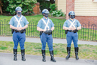 """State police wearing protective facemasks look on as people gather for an anti-lockdown protest organized by the alt-right group Super Happy Fun America near the home of Massachusetts governor Charlie Baker in Swampscott, Massachusetts, on Sat., May 16, 2020. The protest was in defiance of Massachusetts orders mandating face coverings and social distancing and prohibiting gatherings larger than 10 people during the ongoing Coronavirus (COVID-19) global pandemic. The state's stay-at-home order is expected to be updated on May 18, 2020, with a phased reopening plan issued by the governor as COVID-19 cases continue to decrease. Anti-lockdown protests such as this have become a conservative cause and have been celebrated by US president Donald Trump. Many of the protestors displayed pro-Trump messages or wore Trump campaign hats and shirts with phrases including """"Trump 2020"""" and """"Keep America Great."""" Super Happy Fun America, organizers of the protest, are an alt-right organization best known for creating the 2019 Boston Straight Pride Parade."""