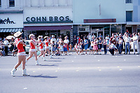 Majorettes in colorful red skits and western hats and boots marching on Congress Avenue during downtown Austin parade, circa 1960s - Stock Image.