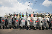 MEXICO CITY, MEXICO - June 11, 2017:  Mexico police officers with barricades march outside Azteca Stadium. USA fans attend the World Cup Qualifier match against Mexico at Azteca Stadium.