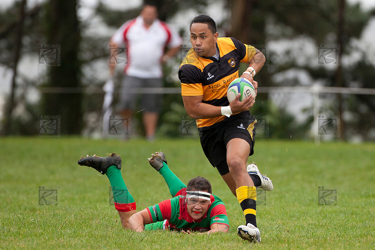 Jamie Baker can only watch from grass level as Sione Olive makes a break upfield.  Counties Manukau Premier Club Rugby game between Bombay and Waiuku played up on the hill at Bombay on March 26th 2011. Waiuku won 57 - 10 after leading 24 - 3 at halftime.