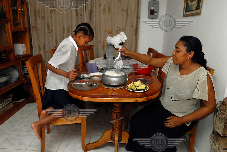 Eight year old Grace Makene and her mother have dinner together.