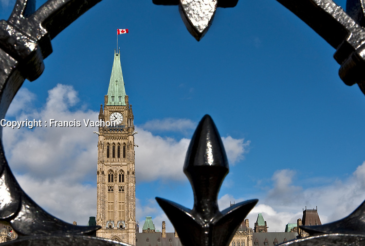 The Parliament Peace Tower is seen through the front fence in Ottawa Monday September 27, 2010. Parliament Hill (colloquially The Hill, in French: Colline du Parlement) is an area of Crown land on the southern banks of the Ottawa River in downtown with a Gothic revival suite of buildings, the parliament buildings, that serves as the home of the Parliament of Canada and contains a number of architectural elements of national symbolic importance.<br /> <br /> PHOTO :  Francis Vachon - Agence Quebec Presse